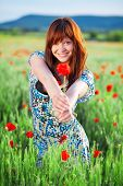 Beautiful smiling teenage girl giving flower to you