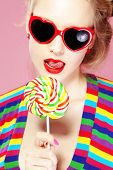 image of lolita  - Glamourous girl wearing heart shaped sunglasses holding lollipop - JPG