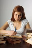 A young pretty student writing on books on the table on a white background