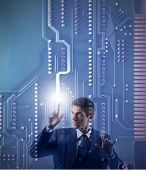 pic of informatics  - businessman touching a digital motherboard - JPG