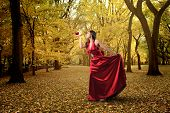 woman in red dress and holding apple in a wood