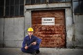 unemployed worker in front of closed workshop