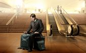 Portrait of a businessman sitting on his luggage in the middle of an airport hall