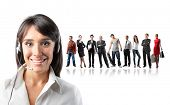 Retrato de um operador feminino sorridente com um grupo de pessoas diferentes sobre o fundo
