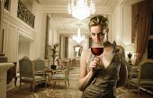 Portrait of a beautiful woman standing in a corridor of a luxury hotel with a glass of wine in her hand