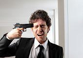 Businessman pointing a gun at his head