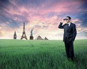 Businessman standing on a green meadow and using binoculars with landmarks from different cities on the background poster