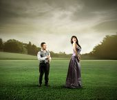 Beautiful woman and dwarf standing on a green meadow