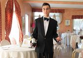Young waiter showing a bottle of wine in a restaurant