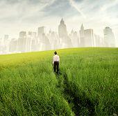 Empresario caminando en un prado verde con paisaje al fondo