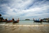 Long-tailed boats on the beach waiting for tourist poster