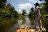 CHIANG MAI, THAILAND - APRIL 23: A bamboo raft and his handler negotiates the meandering river downs