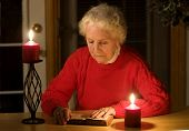 stock photo of old lady  - elderly lady sitting in candlelight reading the bible - JPG