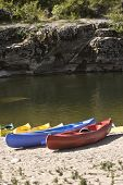 colorful touring canoes on river bank