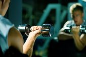 Young with dumbbells, seeing himself in mirror (focus on dumbbells)