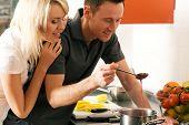 Casal jovem cozinha (neste caso: molho de morango de sobremesa)