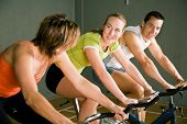 Three People Cycling In A Gym Or Fitness Club, Dressed In Colorful Clothes; Focus On Girl In The Mid