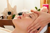 Beautiful woman enjoying a face massage competently carried out in a spa - in the background lots of