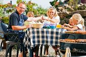 foto of bbq party  - Family having a barbecue in the garden - JPG