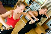 Couple doing their training with dumbbells in the gym