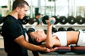 pic of personal trainer  - Woman with her personal fitness trainer in the gym exercising with dumbbells - JPG