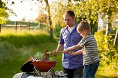 Family - father and son - having a barbecue party, the child is turning meat and sausages, both havi