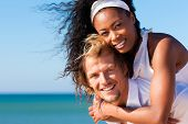Couple in love - Caucasian man having his African-American woman piggyback on his back under a blue