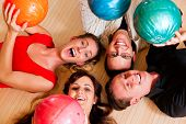 Grupo de cuatro amigos en una bolera, divertirse, con sus bolas de bowling por encima de ellos