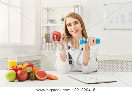 poster of Young dietitian with apple and dumbbell at clinic. Smiling woman nutritionist holding fruit and sport equipment. Weight loss, healthy eating and slimming concept