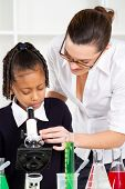 friendly teacher helping primary schoolgirl in science class
