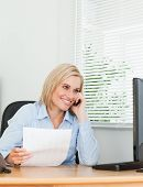 Businesswoman smiling at screen while phoning and holding a paper in her office