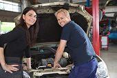 Retrato de cliente feliz feminino e mecânico na garagem