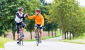 Racing cyclists after sport and fitness workout giving high five in finish poster