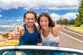 Car happy road trip young drivers driving in convertible cabriolet car. Smiling couple doing thumbs  poster