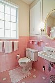 dated bathroom with pink tile and white wood
