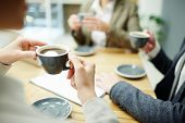 Cup of black tea or coffee held by businesswoman during coffee-break with colleagues poster
