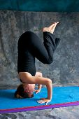 Young Woman Doing Advanced  Yoga Asana Sirsasana Or Headstand