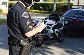 picture of glock  - a motorcycle police officer writing a ticket at a stop - JPG