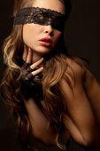 Mooie naakte sexy vrouw met zwarte opengewerkte kant in de duisternis