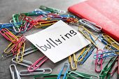 Note with word Bullying and paper clips on grey background poster
