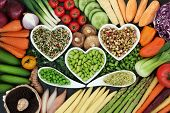 Healthy diet superfood concept with fresh vegetables loose and in heart shaped and curved bowls with poster