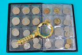 Magnifying Glass And Album With A Collection Of Coins