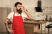 How To Turn Cooking At Home Into Habit. Man Bearded Hipster Red Apron Stand In Kitchen. Kitchen Furn poster