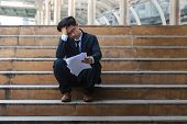 Depressed Stressed Young Asian Business Man In Suit With Hands On Head Sitting On Stairs. Unemployme poster