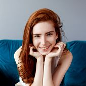 Beautiful Smiling Redhead Woman Sitting On The Blue Couch At Home. poster