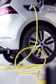 Close Up Of Power Cable Charging Environmentally Friendly Zero Emission Electric Car In Garage poster