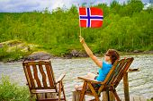 Mature Woman Relaxing Outdoor, Holding Norwegian Flag, Sitting On Wooden Chair On Lake Fjord Shore.  poster