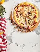 Hot seafood pizza with squid, mussels and fish fillet on wooden plate top view. Pizza ai frutti di m poster