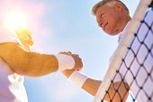 Active senior tennis players greeting each other by shaking hands with yellow lens flare in backgrou poster
