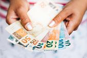 Brazilian Money - Real Notes - Brazilian Currency - Finance Concept - Investments - Wealth - Woman H poster